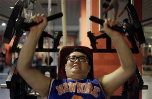 A man lifts weight as part of his training during a six-week programme in an exercise room at the Bodyworks weight loss campus in Beijing August 26, 2011.         REUTERS/Soo Hoo Zheyang